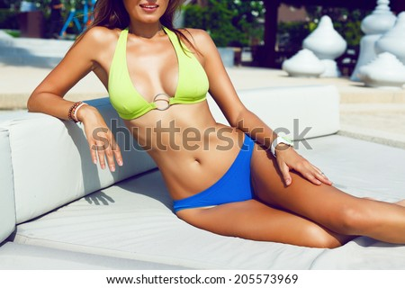 Young sexy tan woman with perfect body and big boobs getting sunbathe at luxury resort on vacation in hot tropical country, wearing trendy bright bikini.