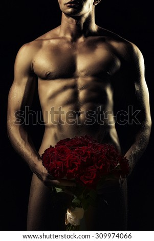 Young sexy undressed man with beautiful strong muscular body holding big fresh red rose flowers bouquet on genitals standing on black background, vertical picture
