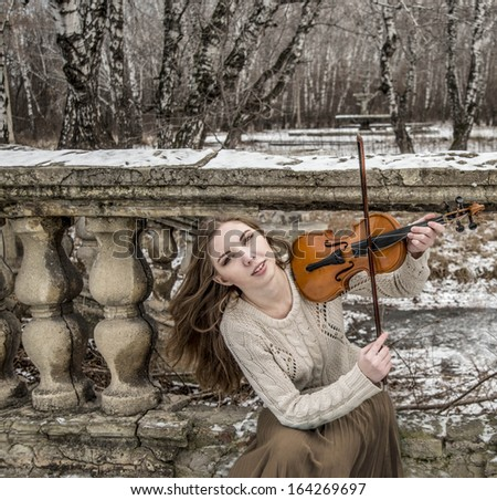 Young sexy with long hair with a broken violin on old retro fence and  stairway in the Gothic style of classicism