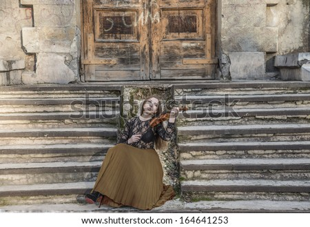 Young sexy with long hair with a broken violin on old retro fence  in the Gothic style of classicism