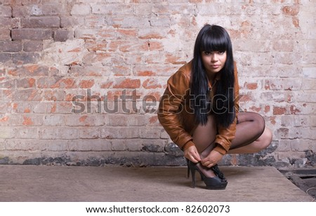 Young sexy woman buttoning shoes in front of a brick wall