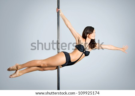 Young sexy woman exercise pole dance against a gray background - stock photo