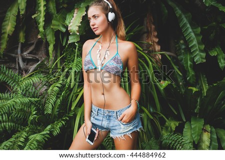 young sexy woman in bikini top and denim shorts, listening to music on headphones, holding smartphone, tanned skin, skinny body, green tropical background, smiling