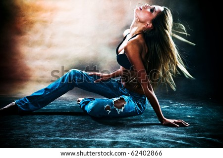 young sexy woman in blue jeans and  brassiere dancing on the floor, studio shot - stock photo