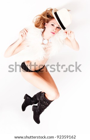 young sexy woman in boots, fur and hat, studio white