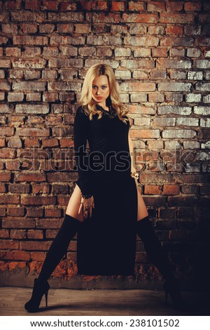 Young sexy woman in long black dress on brick wall background. Warm colors. #238101502