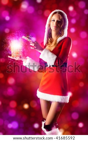 Young sexy woman in santa clothing opening magic box.