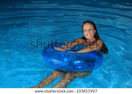 Young sexy woman in the swimming pool at night