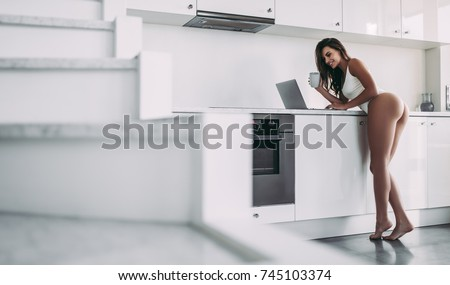 Young sexy woman in underwear is standing on light modern kitchen with laptop and cup of coffee in hands. Back view of sports woman with perfect figure and 