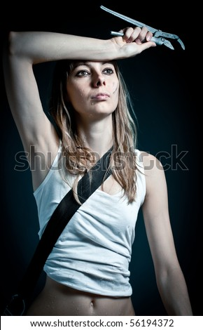 young sexy woman  in white undershirt with working tool in hand against dark background