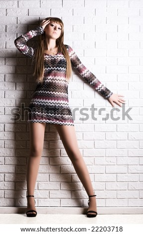 Young sexy woman on white brick wall background.
