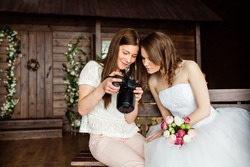 young sexy woman photographer shows the bride had just taken photos