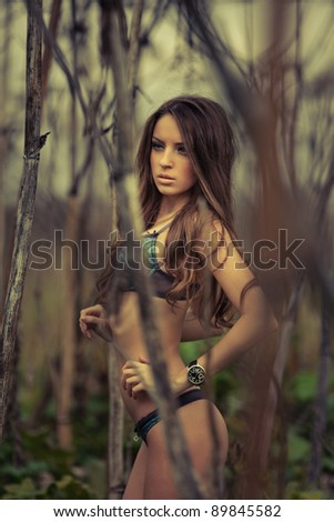 Young sexy woman posing in thickets