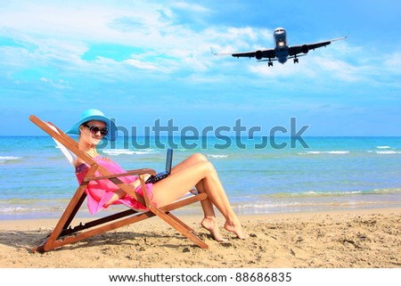 Young sexy woman Relaxing on the beach with her laptop and an airplane passing behind her - Travel concept