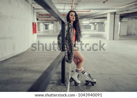 young sexy woman rollerskating in an urban looking garage and posing in a hipster like matter