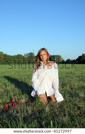 Young sexy woman sitting on the grass