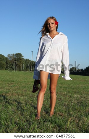 Young sexy woman walking on the grass