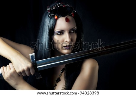 Young sexy woman warrior holding sword in hands with long healthy black hair.