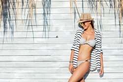 young sexy woman wearing hat, sunglasses and bathing suit marine style, standing on wooden vintage wall with reed in full sunlight