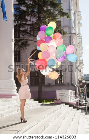 Young sexy woman with latex balloons, urban scene, outdoors