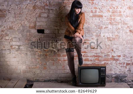 Young sexy woman with retro TV in the old brick wall.