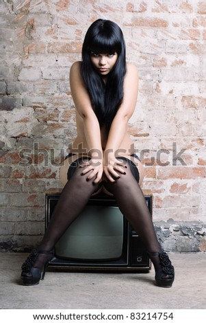 Young sexy woman with retro TV in the old brick wall. - stock photo