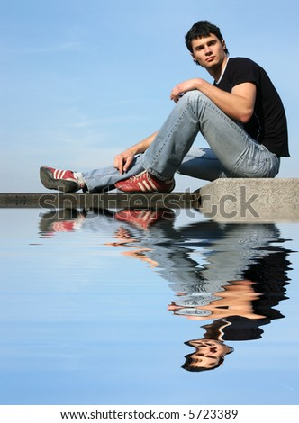 Young sexy young man sitting on the stone blocks with reflection