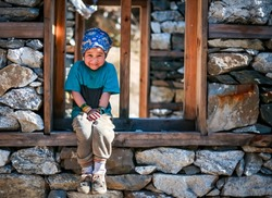Young Sherpa Girl with Bandana Headband Sits on the window frame of under construction house and smiles at the camera in remote Manaslu region of Nepal. selective focus