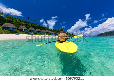 Young shirtless caucasian boy kayaking at tropical sea on yellow kayak