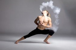 Young shirtless man dancer vaping and blowing smoke on grey