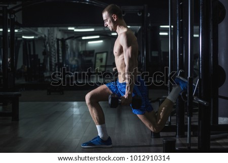 Young shirtless man doing split squats with weights