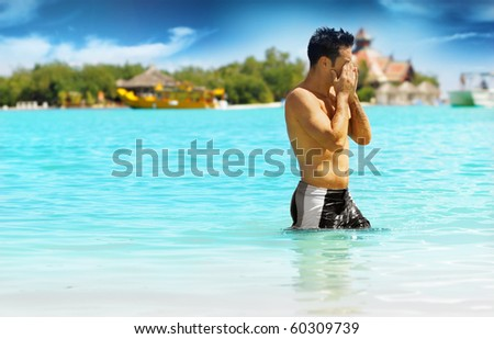 Young shirtless man relaxing in tropical warm resort waters