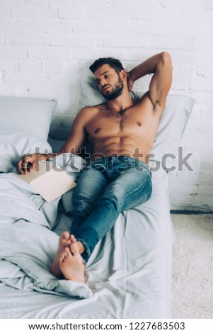 young shirtless muscular man sitting with book on bed at home