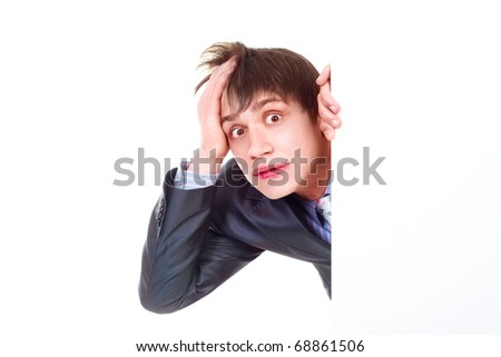 young shocked businessman hiding behind a big blank sheet of paper