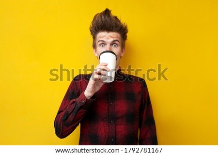 young shocked guy drinks invigorating coffee and is surprised at a yellow isolated background, a man drinks an energy drink Stock foto ©