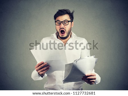 Young shocked guy in glasses looking at papers bank documents with list of bills and fees and feeling stressed on gray background