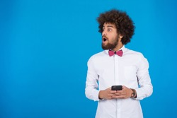 Young shocked man holding his phone looking away surprised with open mouth, on a blue background.