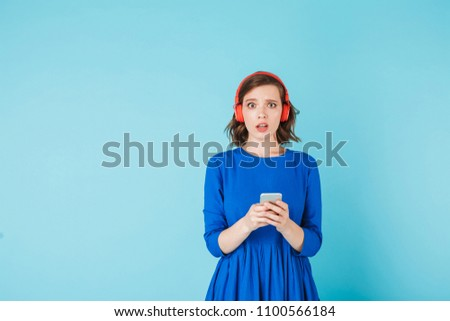 Young shoked lady in dress and red headphones standing with cellphone and amazedly looking in camera on over blue background