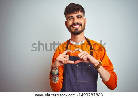 Young shopkeeper man with tattoo wearing apron standing over isolated white background smiling in love showing heart symbol and shape with hands. Romantic concept.