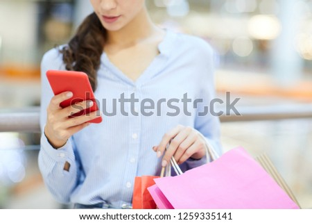 Young shopper with smartphone and paperbags scrolling through new messages and notifications after shopping