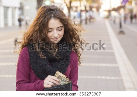 Shutterstock young shopper woman taking out money from wallet on street
