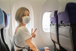 Young short-haired Asian woman in white wearing a face mask for protective Covid-19 sitting on an airplane window seat showing two-finger in V shape sign on the left hand at the camera during flight.