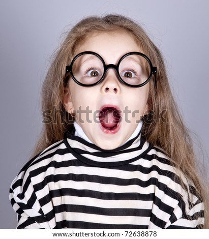 Young shouting child in glasses and striped knitted jacket. Studio shot.