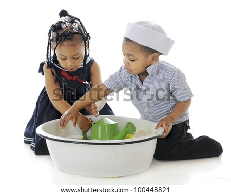 """Young sibling """"sailors"""" playing across each other in a tub filled with water and water toys.  On a white background."""