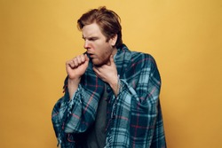 Young Sick Guy Wrapped in Checkered Plaid Coughing. Ill Handsome Person Feels Uncomfortably Unhealthy covering in Blue Wrap Isolated on Yellow Background. Concept of Cold