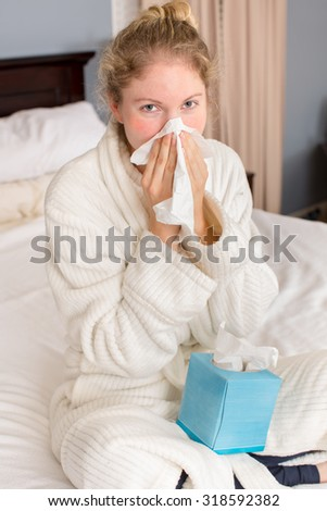 young sick woman holding tissue ...