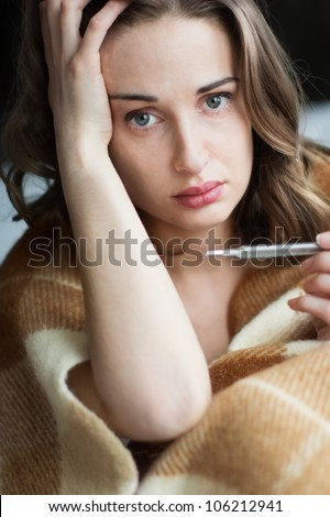 Young sick woman in blanket with shallow depth-of-field. Ill young woman in bed