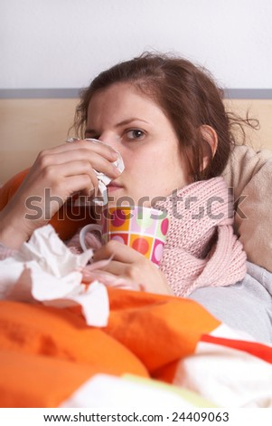 Young sick woman lying in bed. She is staying home from work.