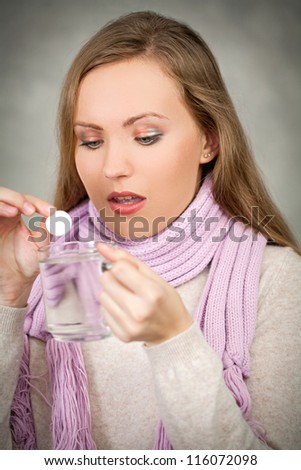 Young sick woman puts aspirin in cup of water - stock photo