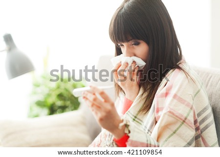 Young sick woman with cold and flu, she is blowing her nose and measuring her body temperature